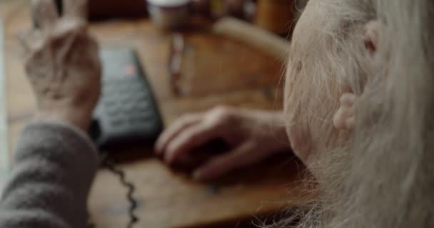 detailní záběr starší ženy, jak si drží telefon u ucha.