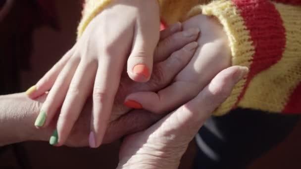 Junge Hände massieren sorgfältig alte Hände mit gelber Haut und großen Nägeln.