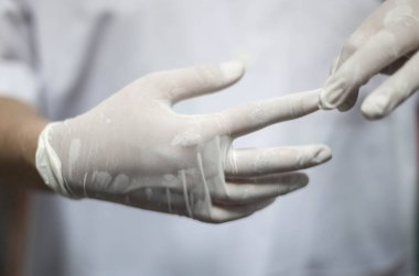 Doctor female taking off medical surgical sterile gloves on white background, For protection Coronavirus (COVID-19) pandemic. Medicine and healthcare concept