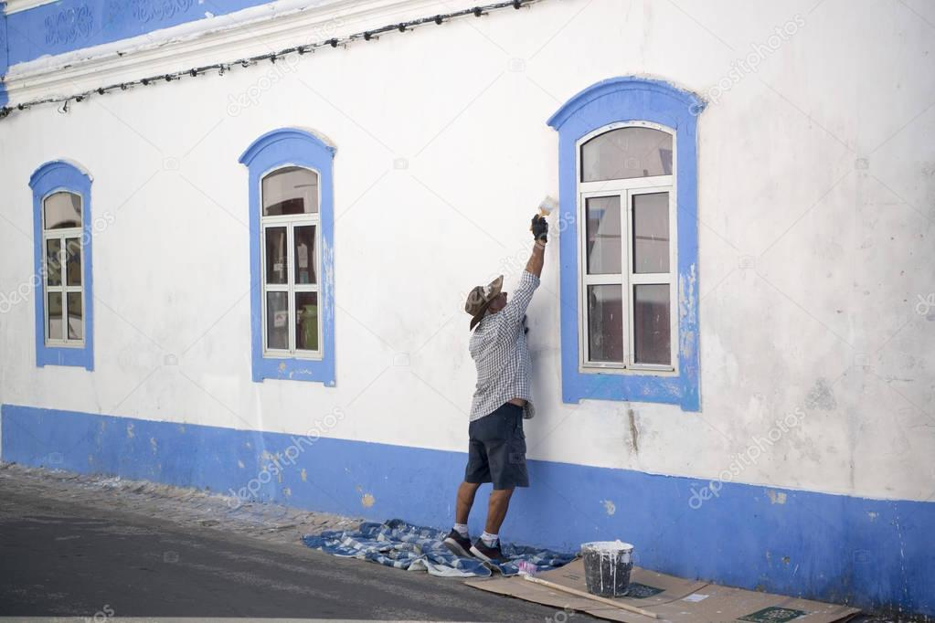 a man painting his house