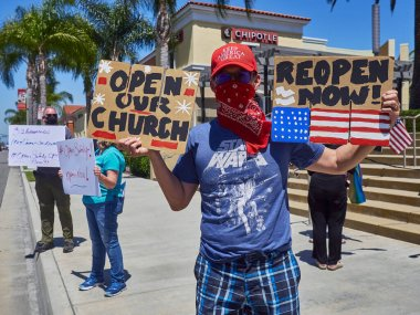 SANTA ANA, California / USA - April 24, 2020: Anti-shutdown protesters and their families gather at a street corner against the stay at home order in California.