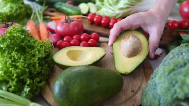 Ruční kladení Cut Avokádo na stůl s čerstvou zeleninou