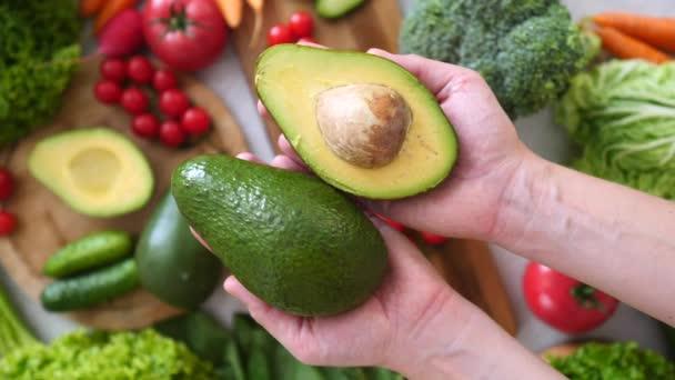 Női kéz fogja a szeletelt avokádót. Szerves vegán ételek.