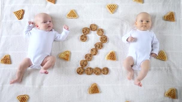 Dvojčata ležící spolu ve vaflích a sušenkách.