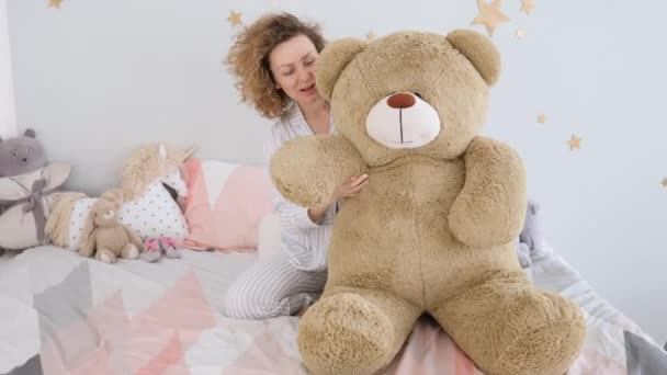 Young Beautiful Girl In Pajamas Hugging Big Bear Soft Toy In Bed