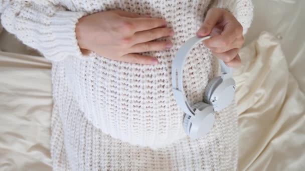 Těhotná žena dávat sluchátka na břicho během těhotenství.