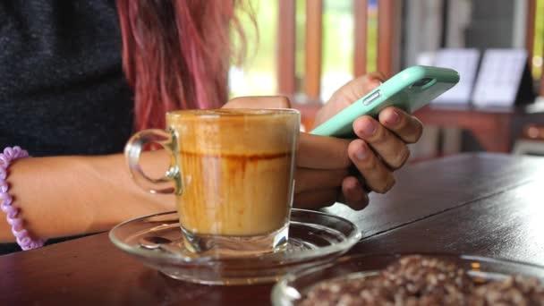 Žena Ruce pomocí chytrého telefonu s kávovým pohárem v kavárně