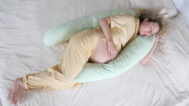 Šťastná těhotná žena spí na mateřském polštáři v posteli