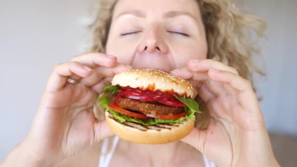 Young Woman Eating Vegan Hamburger. Junk Food Alternative.
