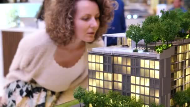Žena vybírá nový byt při pohledu na budovy miniatury. Closeup.