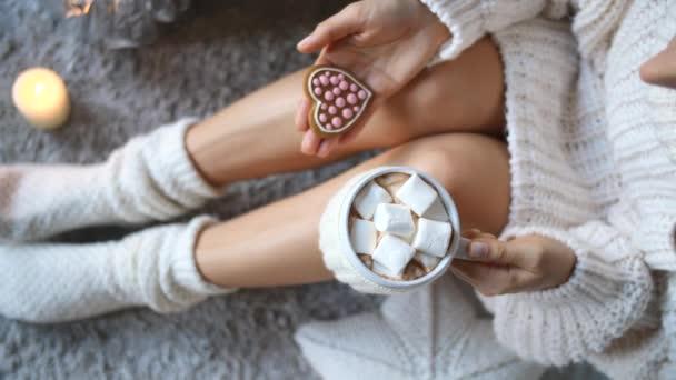 Frauenbeine in Stricksocken mit einer Tasse heißer Schokolade entspannen zu Hause.