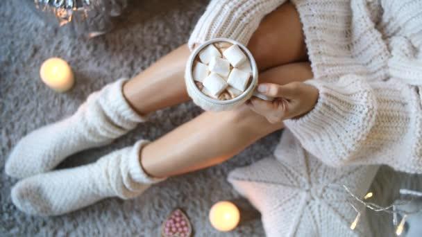 Šálek horké čokolády s marshmallow a ženské nohy v útulné pletené ponožky