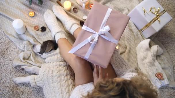 gemütlich gemütlichen Lebensstil. junge Frau mit Geschenkbox zu Hause in Strickkleidung.
