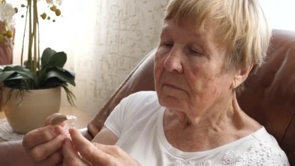 Senior Woman Holds hallókészülék.