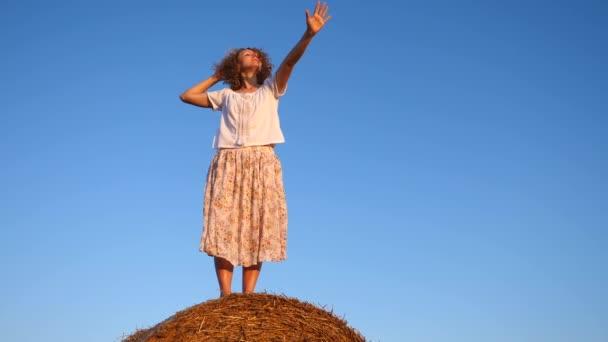 Fiatal boldog nő álló karokkal emelt ellen kék ég