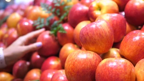 Közelkép a női kéz kiválasztása alma gyümölcs a szupermarketben