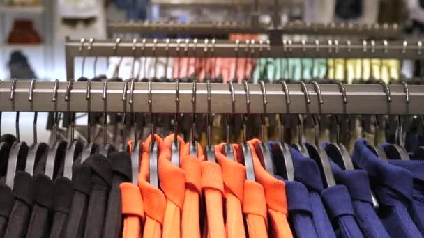 Detailní záběr barevných oblečení na závěsy v obchodě s oblečením