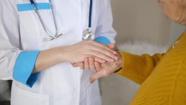 Arzt hält Hand einer älteren Patientin und tröstet sie