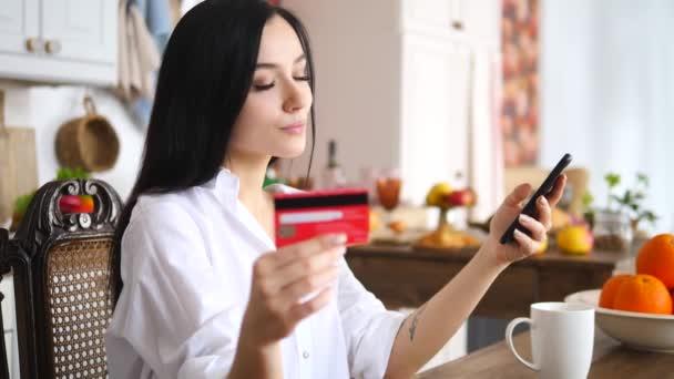 Online fizetési szolgáltatások koncepciója. Fiatal nő használ okostelefon és hitelkártya otthon.