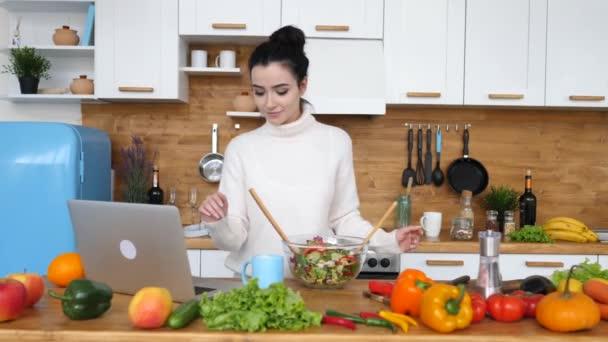 junge Frau kocht mit Laptop in Küche gesunde Lebensmittel.