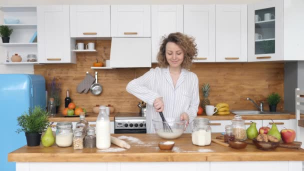 Mladá žena vaření snídaně v dopoledních hodinách v kuchyni.