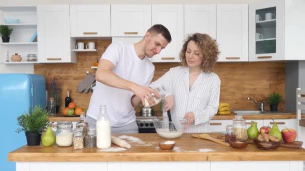 Mladý usmívající se pár dělat palačinky spolu v kuchyni v dopoledních hodinách