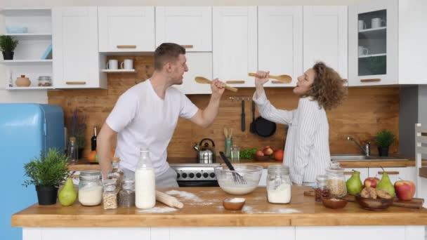 Mladá rodina pár tanec a zpěv v kuchyni doma