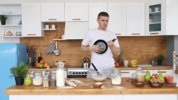 Young Man Playing On Ukulele Using Pan While Cooking Breakfast On Kitchen.