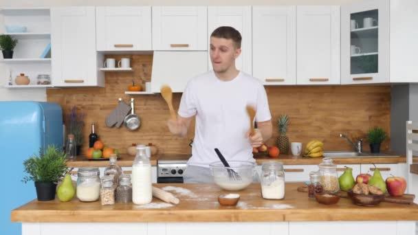 Vicces fiatalember tánc és dobolás a konyhában, miközben főzés élelmiszer otthon.