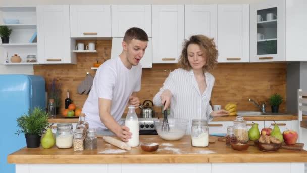 Mladý pár vaření snídaně společně v kuchyni ráno