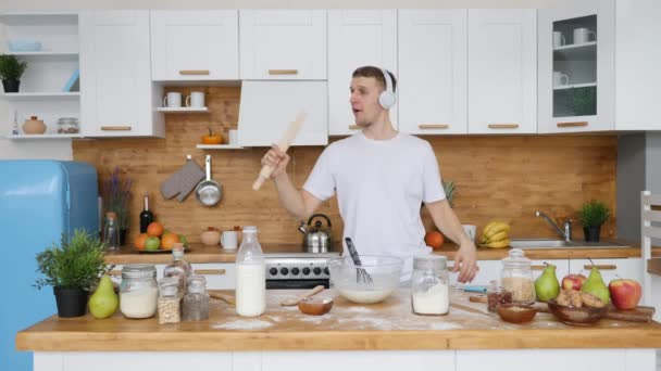 Mladý veselý muž nosí sluchátka a zpívá v kuchyni.