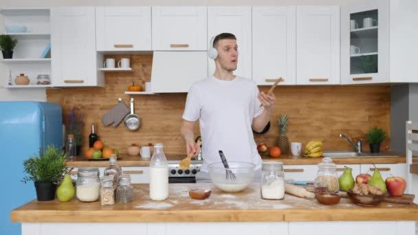 Jó reggelt koncepció. Fiatal férfi táncol és főz a konyhában.