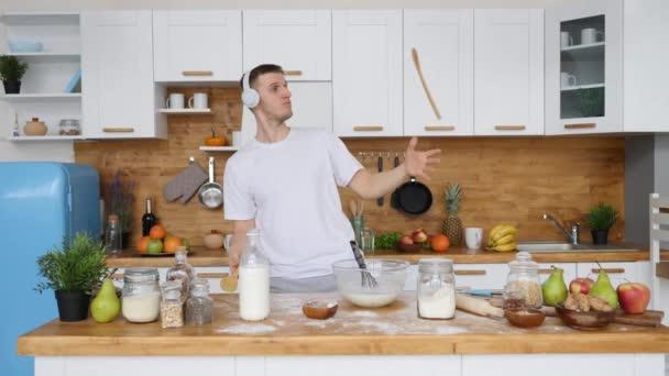 Vidám fiatalember táncol a konyhában Zenét hallgat a fülhallgatóban.
