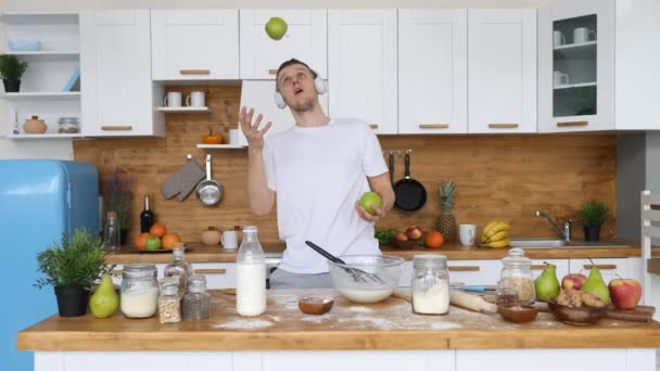 Muž ve sluchátkách a žonglování s jablky. Dobré ráno, koncepce zdravého životního stylu.