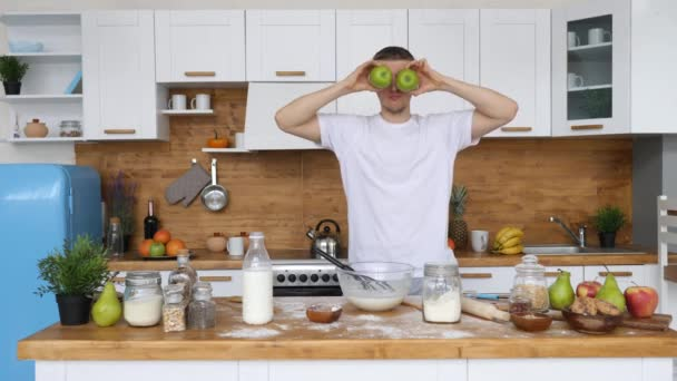 Mladý legrační muž dělat jablečné oči tanec v kuchyni.