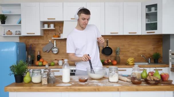 Mladý muž vaření snídaně a poslech hudby ve sluchátkách doma v kuchyni.