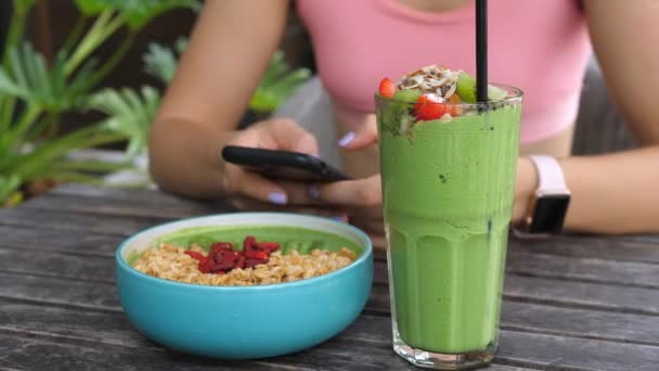 Sport Fitness žena pomocí mobilního telefonu při zdravé Vegan snídaně