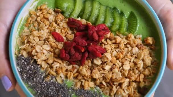 Nahaufnahme einer veganen Avocado-grünen Smoothie-Schüssel mit Müsli, Chia und Goji