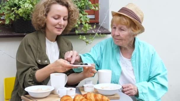 Idős emberek és technológia. Unokám és nagymamám fotóznak..