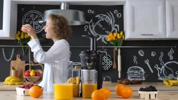 Boldog lány tánc és a friss narancslé a konyhában