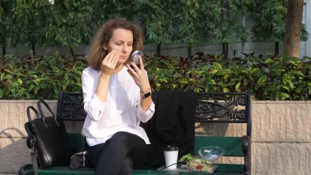 junge Geschäftsfrau sitzt draußen beim Mittagessen und schminkt sich