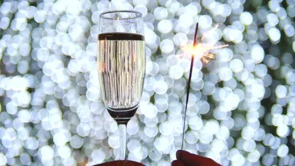 Nahaufnahme von Sektglas und Wunderkerze bei der Weihnachtsfeier.