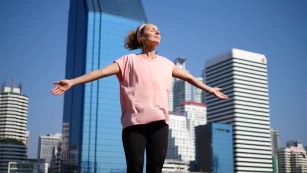 Happy Sport Woman In Wireless Earphones Raising Arms After Workout In City
