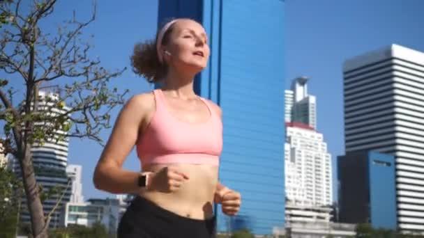 Mladá aktivní žena běží v Smartwatch a bezdrátové sluchátka v městském parku