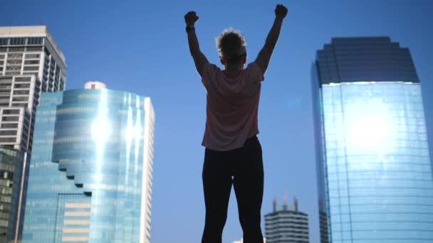 Ženská síla a povznášející koncepce sportovní motivace. Dívka se zdviženými pažemi.