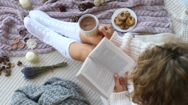Woman In Warm Knitted Socks Reading Book And Drinking Hot Chocolate