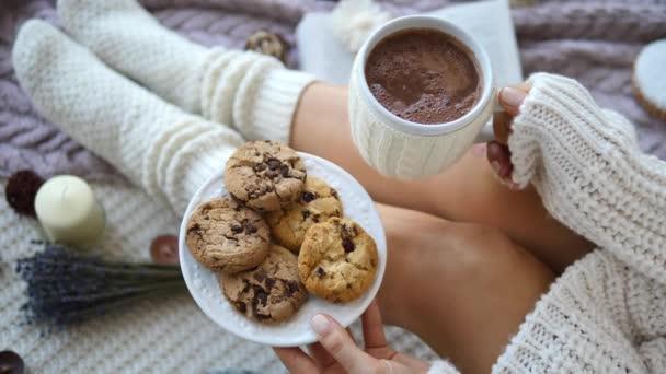trendiges Mädchen in Strickpullover und Socken mit heißer Schokolade und Keksen zu Hause