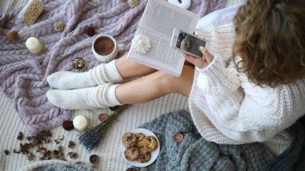Woman Taking Photo With Cellphone Of Flat Lay With Knitted Socks, Cup And Book