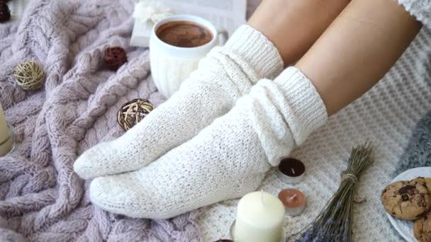 Detailní záběr na ženské nohy v pletených ponožkách doma. Koncept studené zimní sezóny.