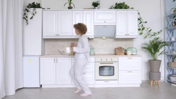 Mladá žena tanec a použití mobilního telefonu v kuchyni.